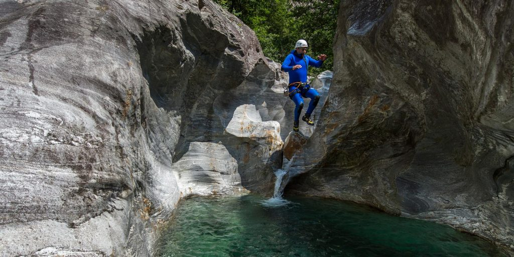jumping into green pool on family canyoning tour